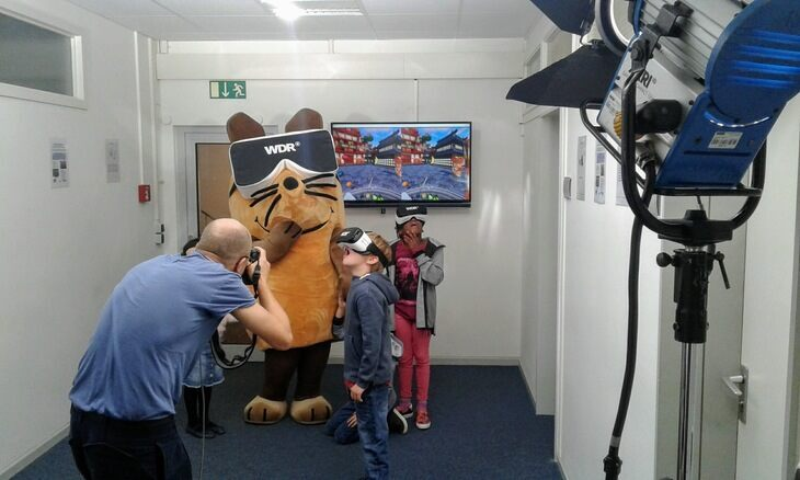 """Die Maus"" and two children with VR- glasses"